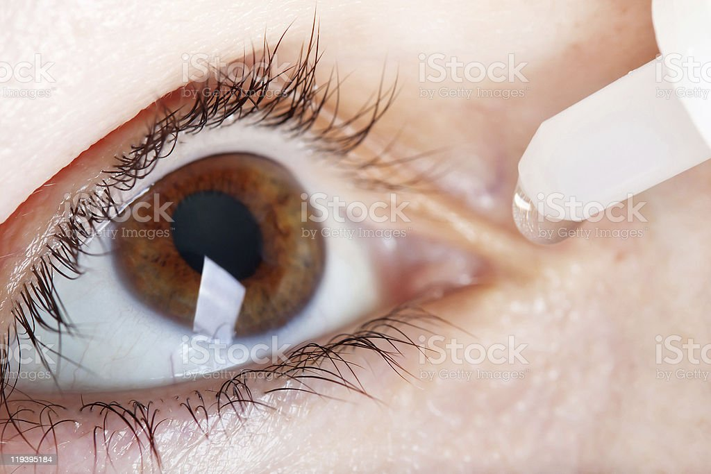 Person with brown eyes using eye drops stock photo
