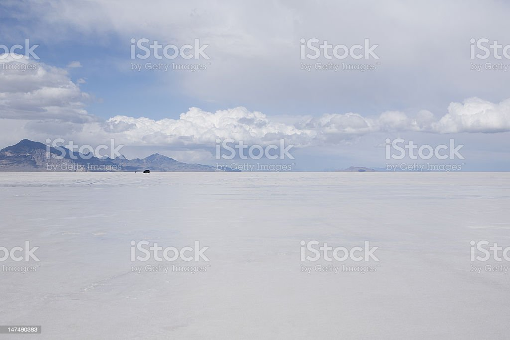 Person with car standing on Bonneville Salt Flats stock photo
