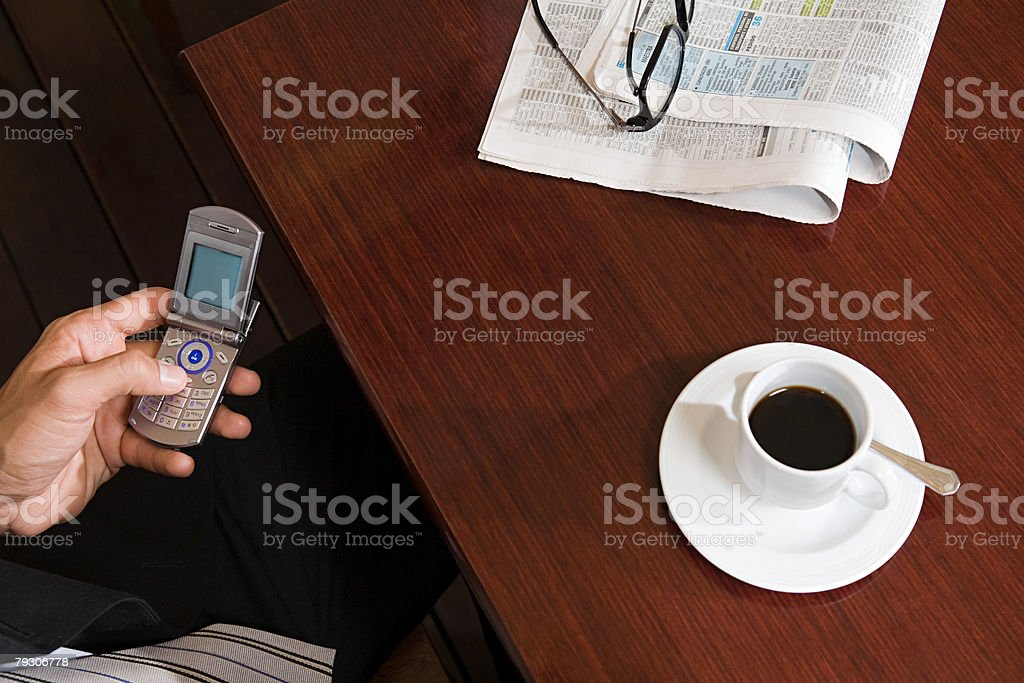 Person with cellphone and coffee stock photo