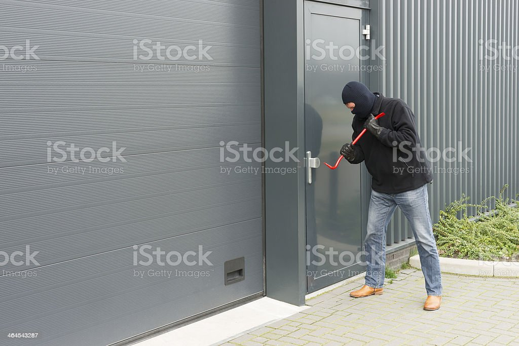Person with crowbar near a warehouse door in middle of day  stock photo
