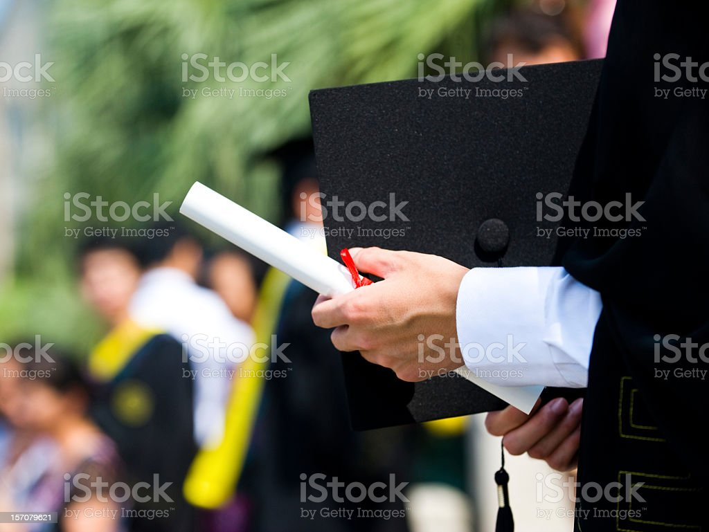 Person with diploma in hand graduating with gown on stock photo