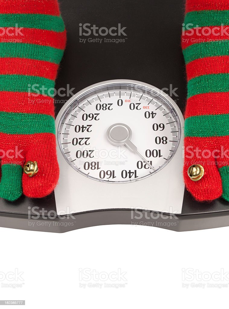 Person with holiday socks standing on a scale, holiday diet stock photo