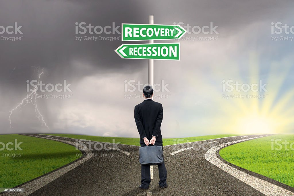 Person with signpost of recession and recovery finance stock photo