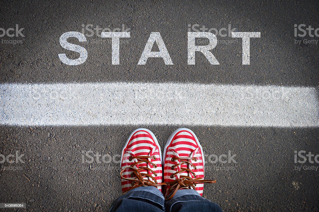 person with sneakers standing in front of the start message stock photo