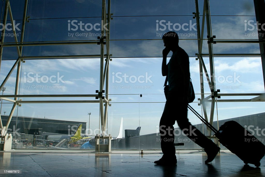 A person with their luggage on the phone at the airport royalty-free stock photo