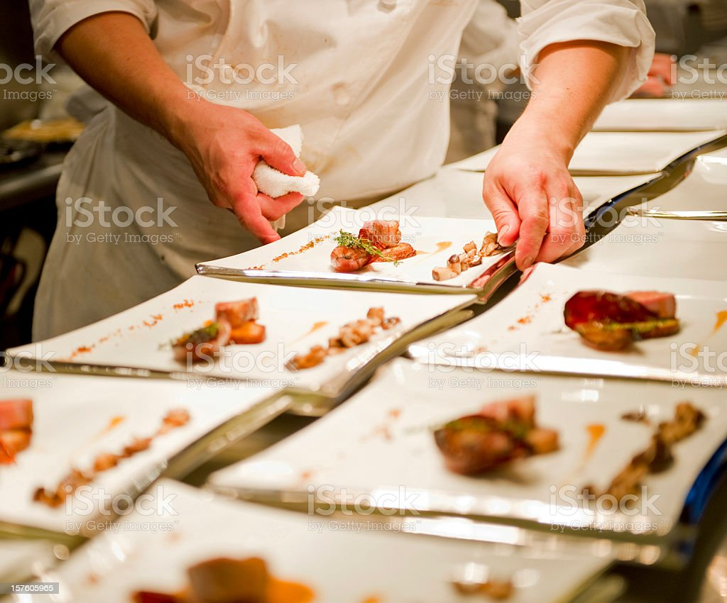 A person working in a kitchen and plating food stock photo
