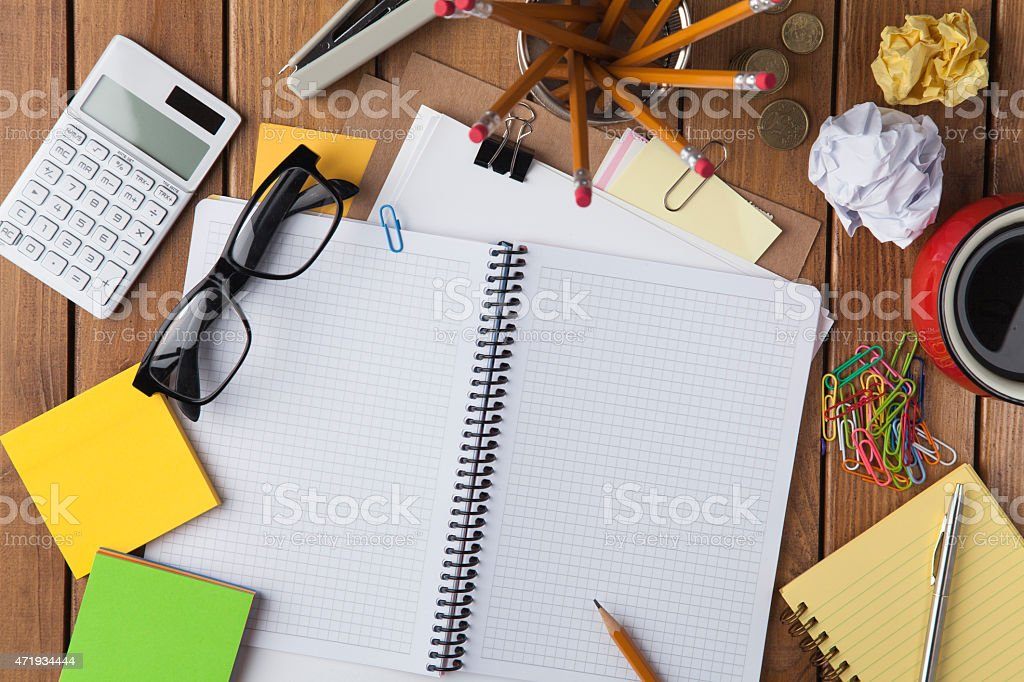 Person working on a wooden table with office supplies stock photo