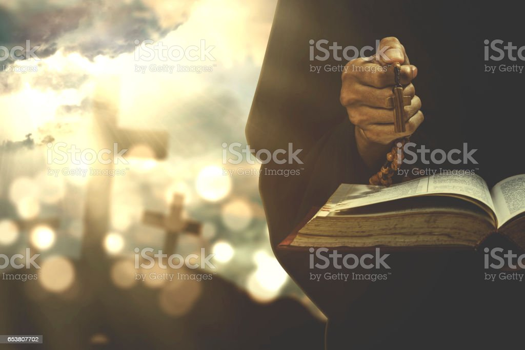 Person worshipping with bible and rosary stock photo