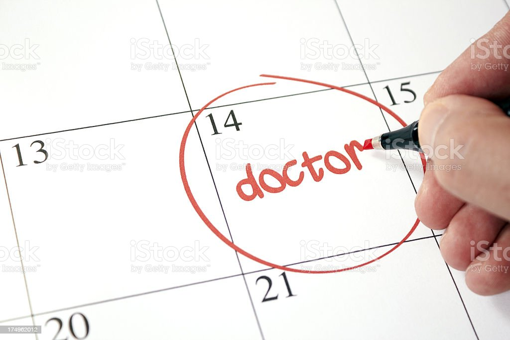 A person writing a doctor's appointment on a calendar royalty-free stock photo