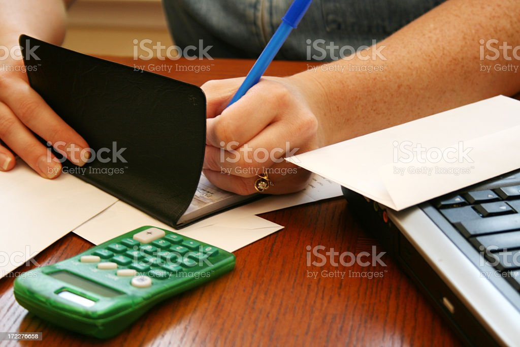 Person writing in a black book next to calculator and laptop stock photo