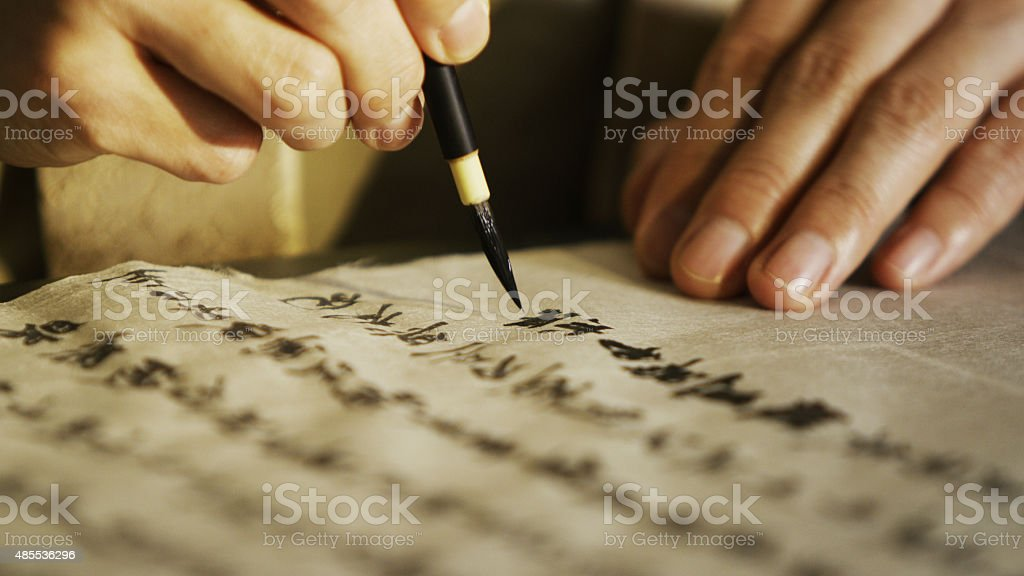 Person writing Japanese calligraphy in traditional style stock photo
