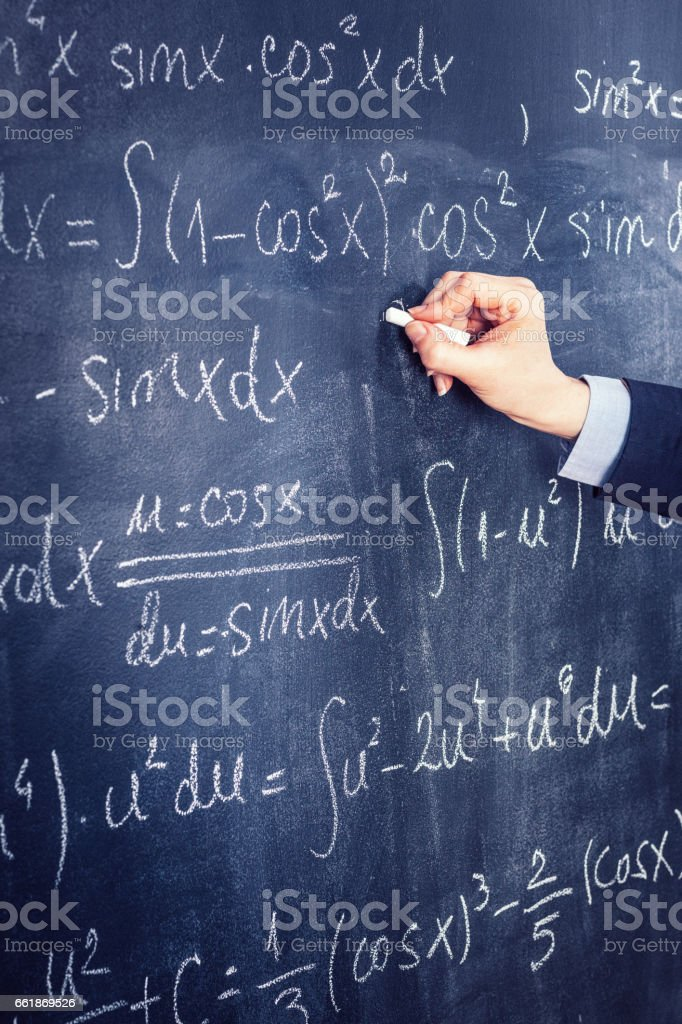 Person writing mathematical equations on the blackboard stock photo
