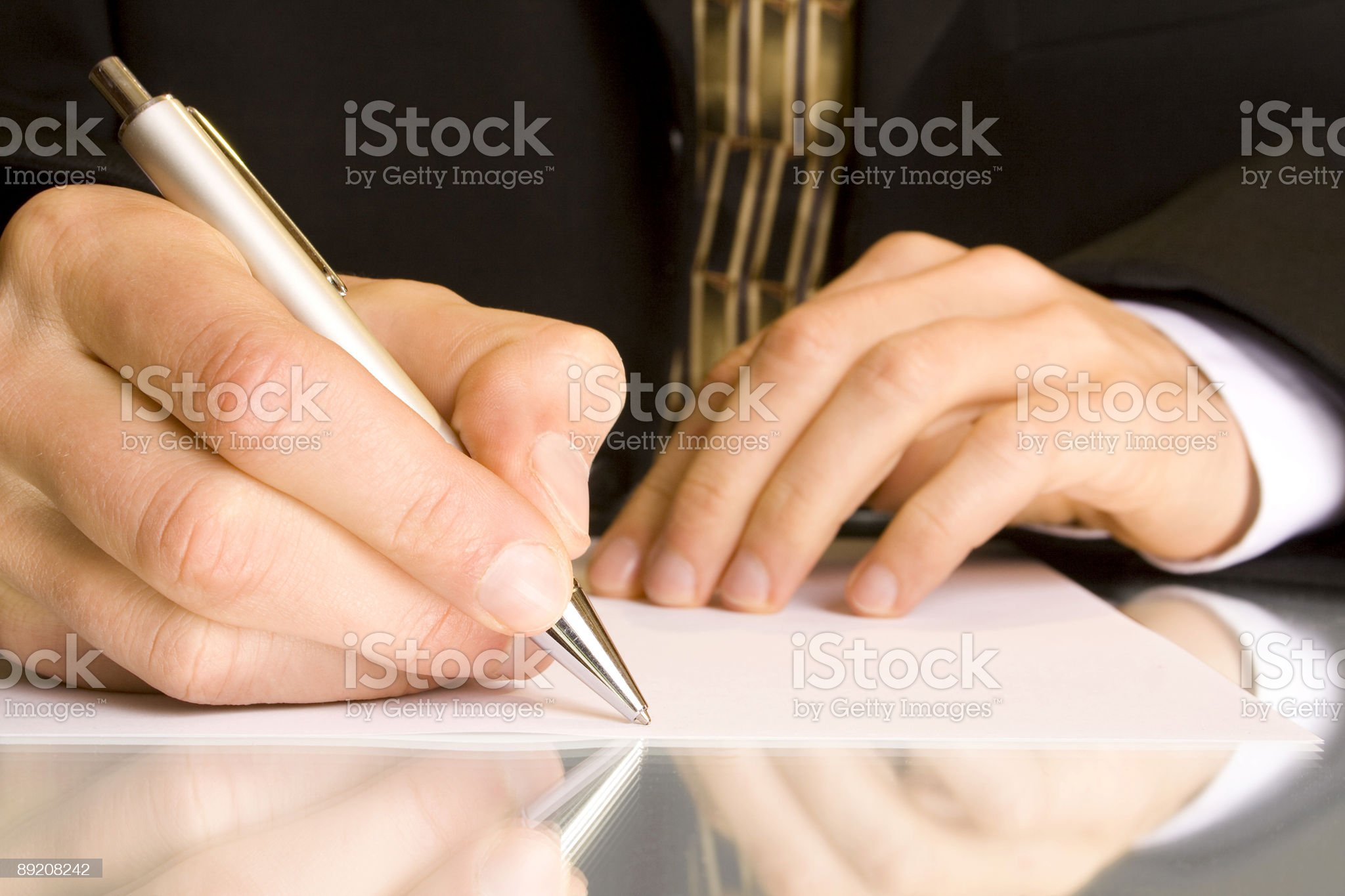 A person writing with a pen on a clean, white sheet of paper royalty-free stock photo