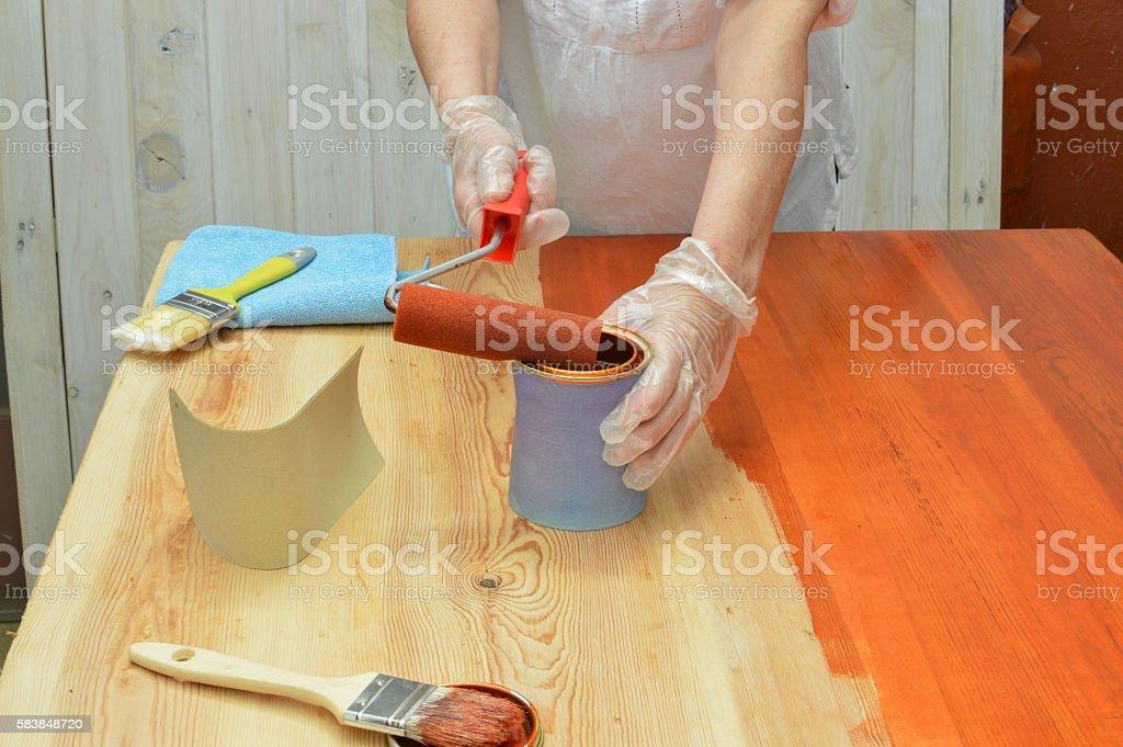 persona pinta con barniz una mesa de madera stock photo