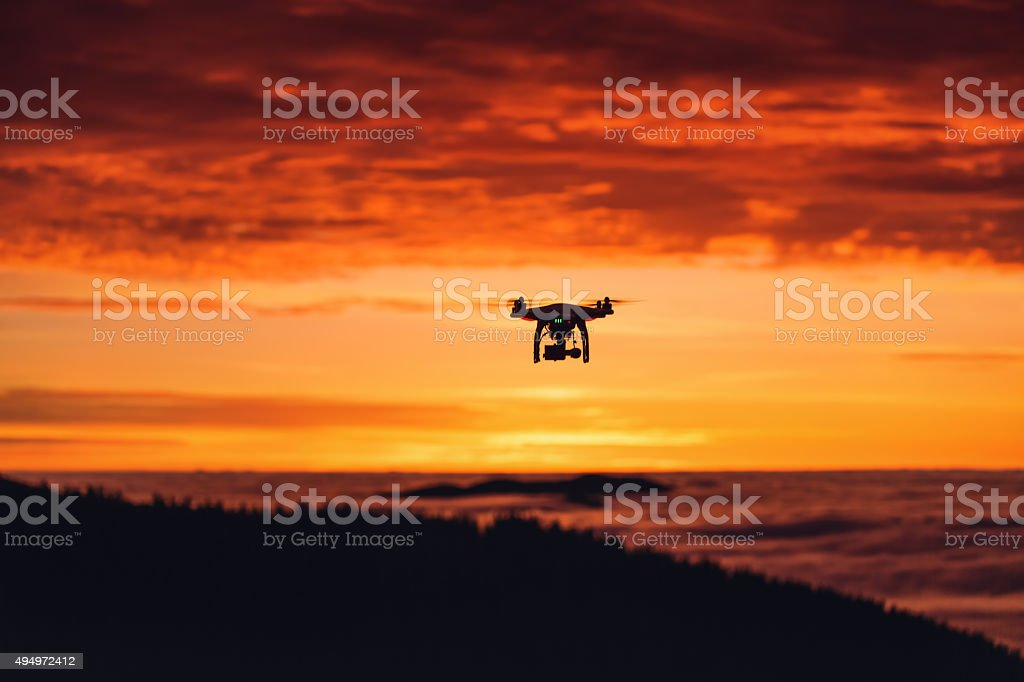 Personal drone flying through the air at sunrise stock photo