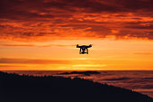 Personal drone flying through the air at sunrise