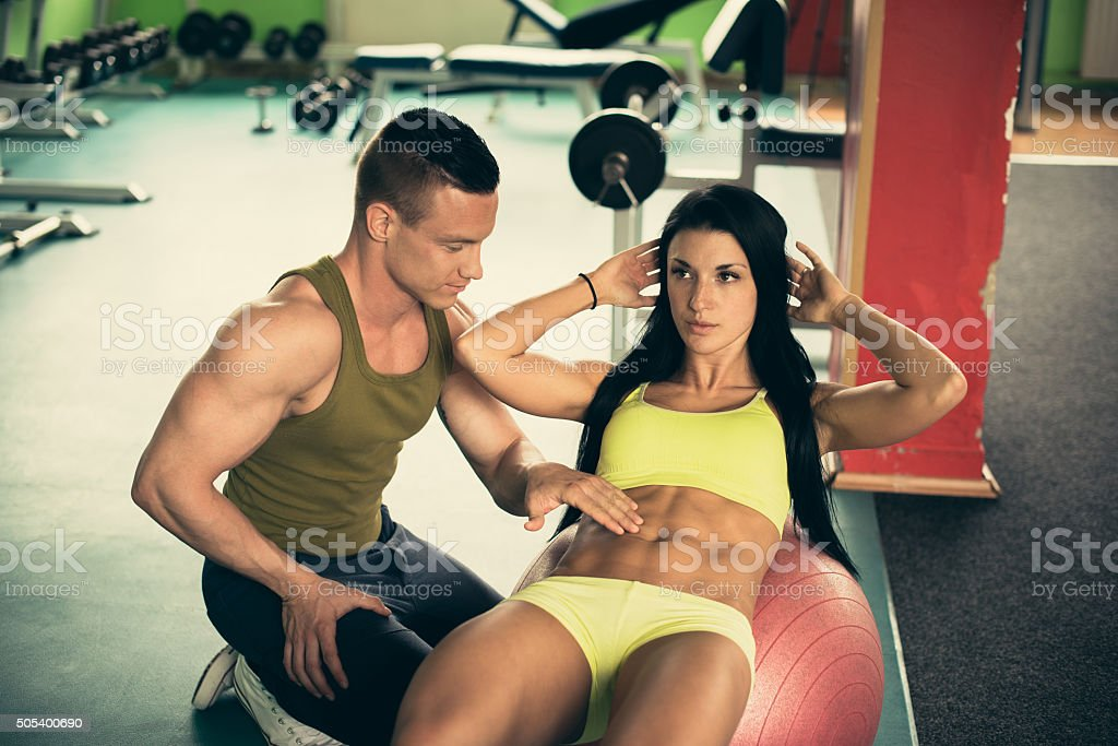 Personal fitness coach trains beautiful woman in gym while she doing...