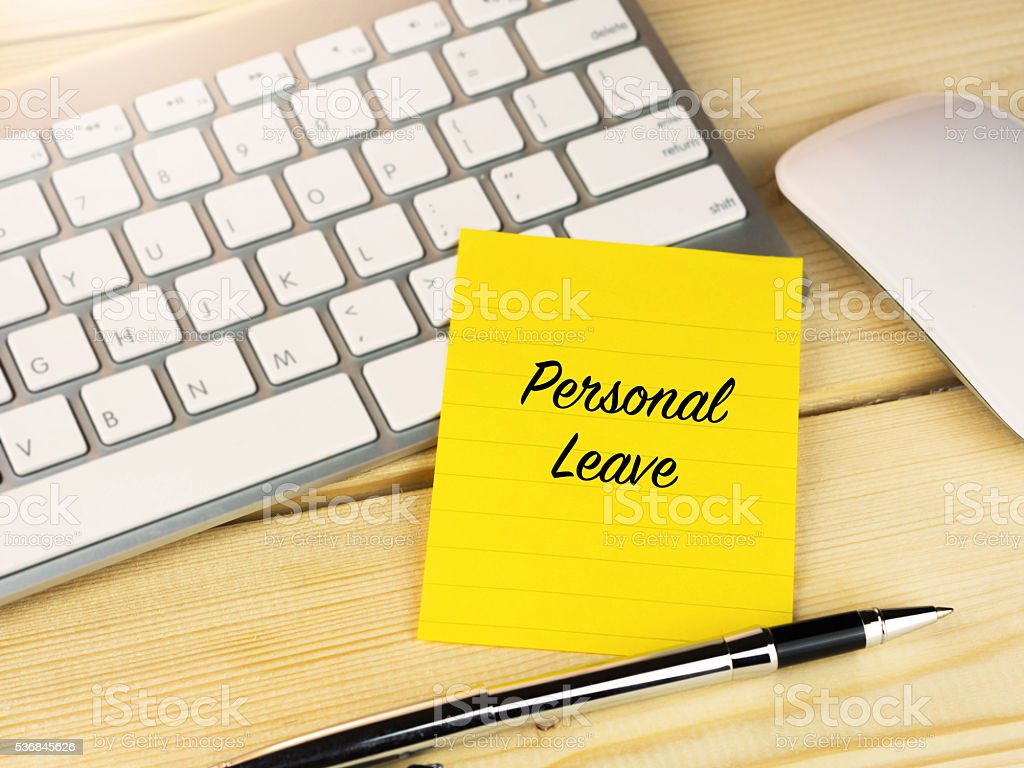 Personal leave on sticky note on work desk stock photo