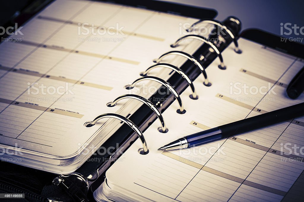 Personal organizer or planner with pen on white background stock photo