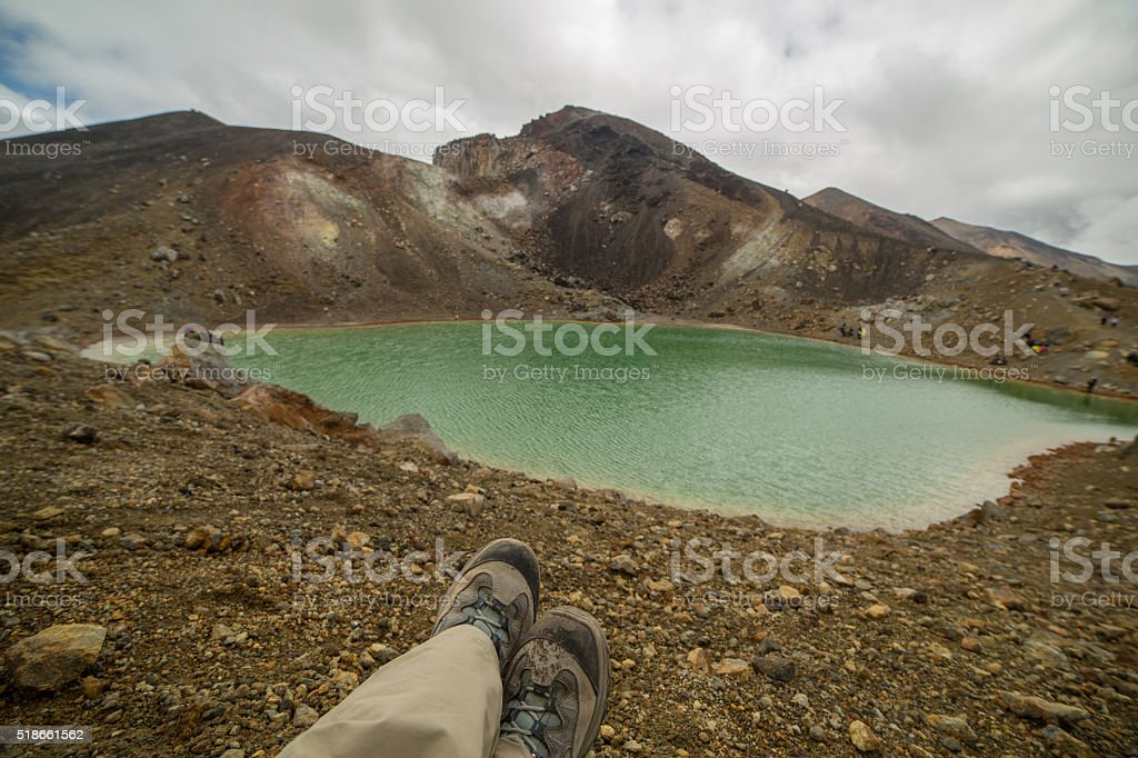 Personal perspective of a hiker relaxing near mountain lake stock photo