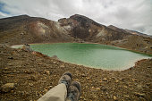 Personal perspective of a hiker relaxing near mountain lake