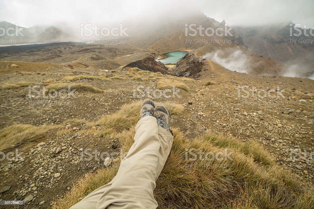 Personal perspective of female hiker relaxing near mountain lake stock photo