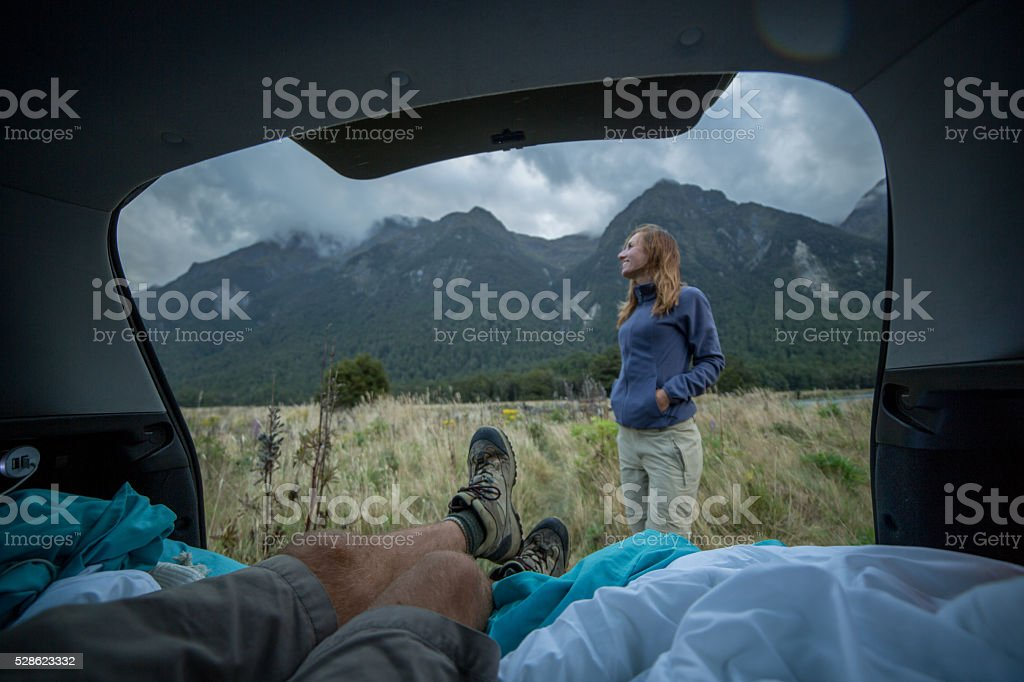 Personal perspective of man lying in car's trunk, mountain landscape stock photo