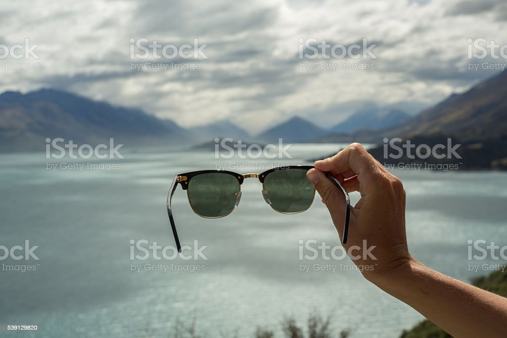 Personal perspective of person holding sunglasses towards nature stock photo