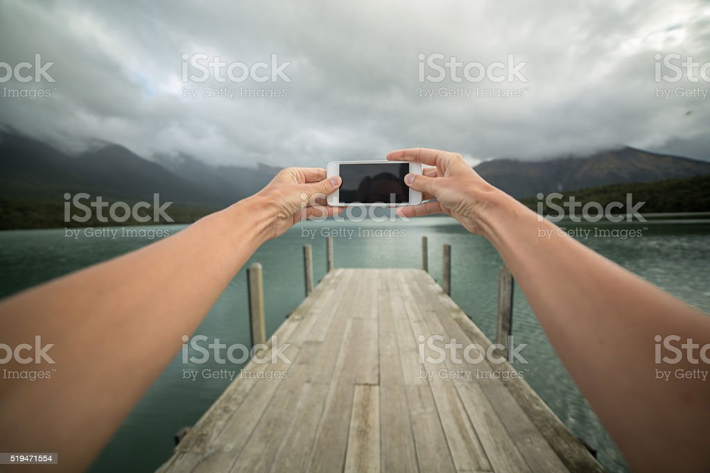 Personal perspective of person taking picture using mobile phone-Pier stock photo