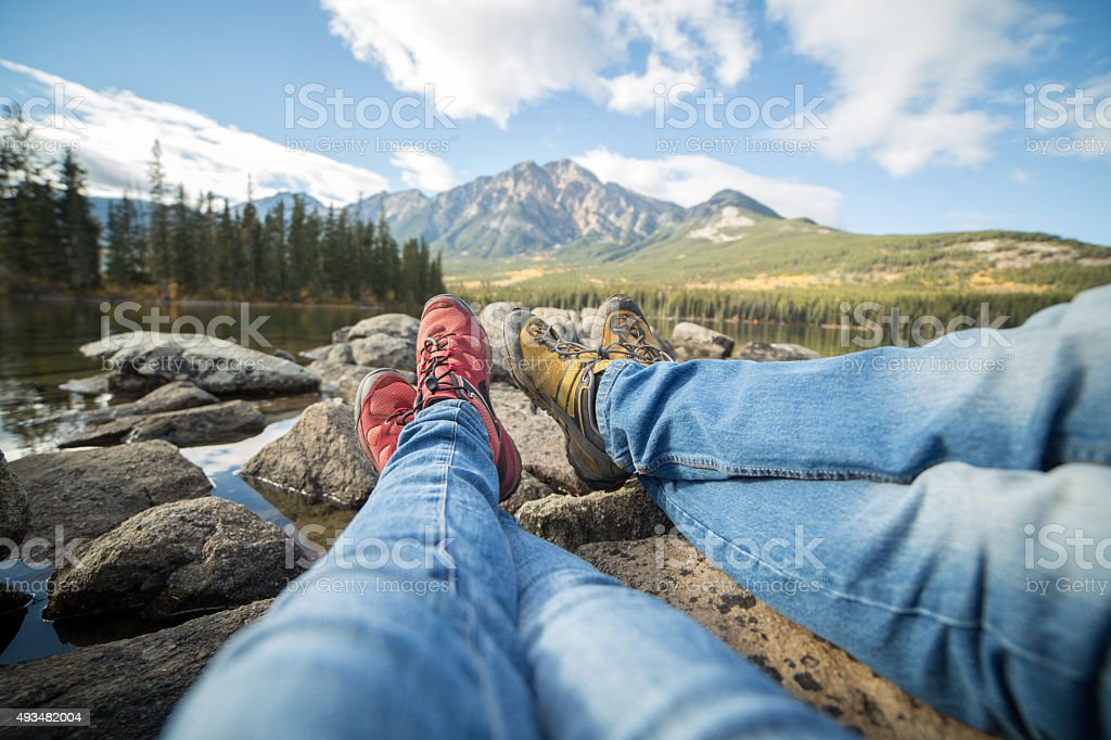 Personal perspective of two people relaxing by the lake stock photo
