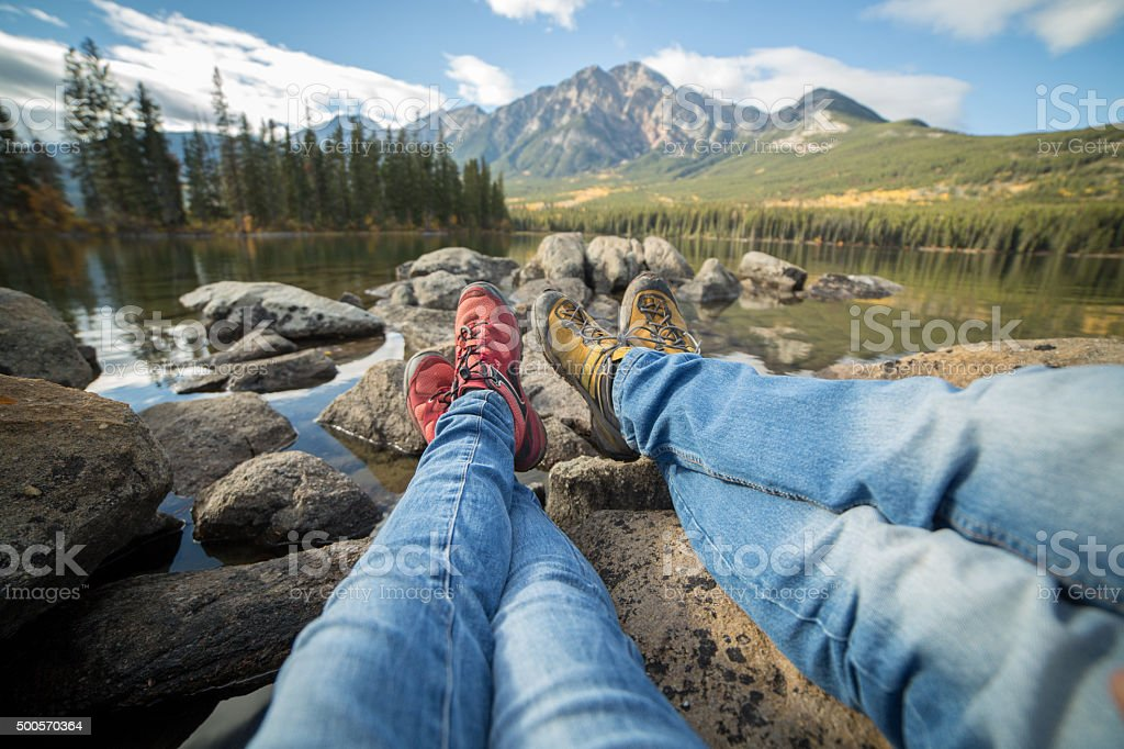 Personal perspective of two people relaxing by the lake. stock photo