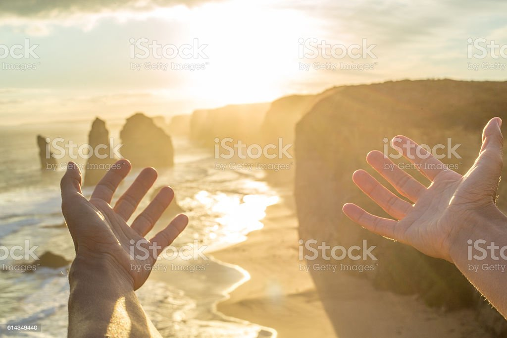 Personal perspective of woman arms outstretched at sunset stock photo