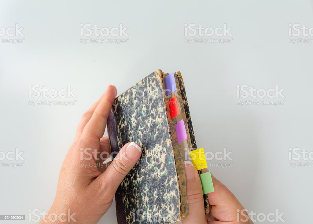Personal perspective woman opening an old color tabed book stock photo
