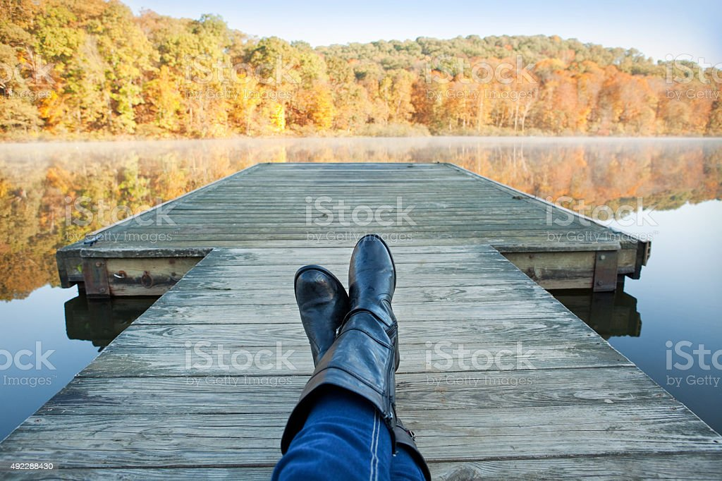 Personal Perspective Woman Resting On Dock Enjoying Fall View stock photo