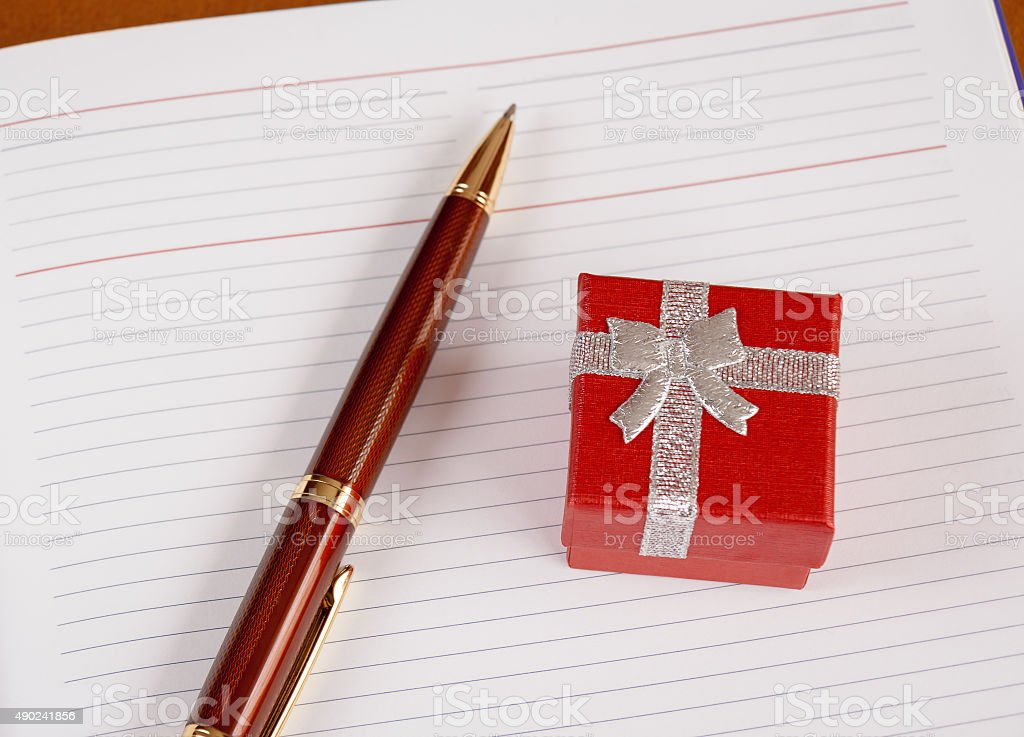 Personal planner with gift box and pen. Selective focus stock photo