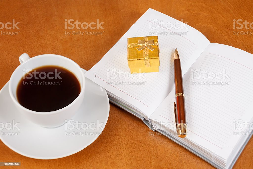 Personal planner with gift box, pen and cup of coffee stock photo