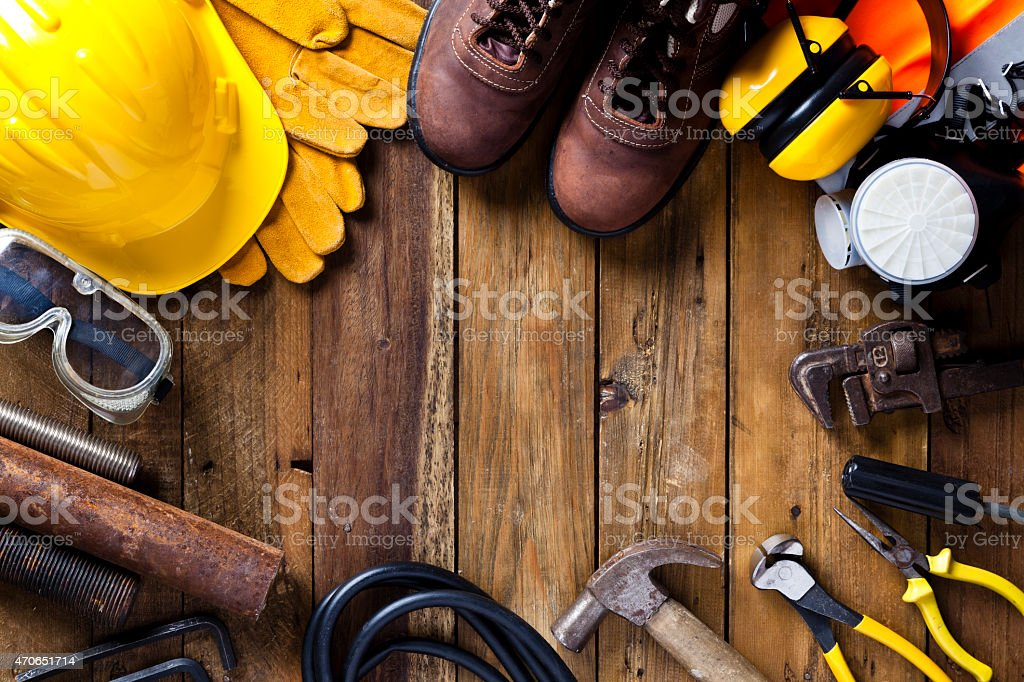 Personal safety workwear and tools border on rustic wood background stock photo