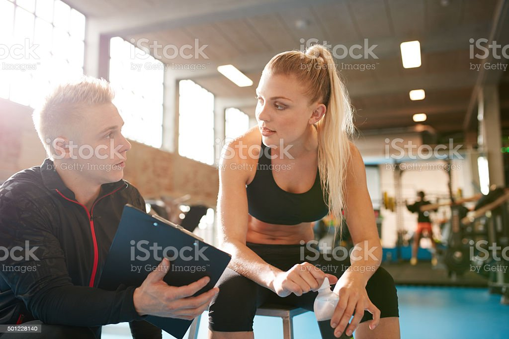 Personal trainer and student discussing fitness plan stock photo