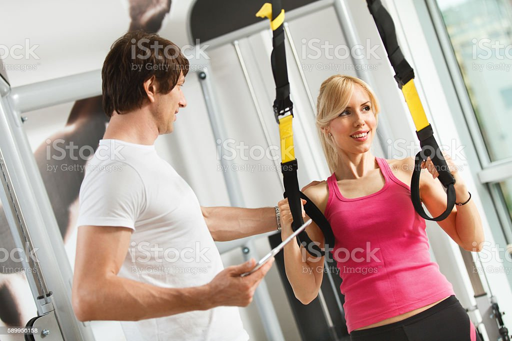 Personal trainer assisting young woman with suspension straps exercises. stock photo