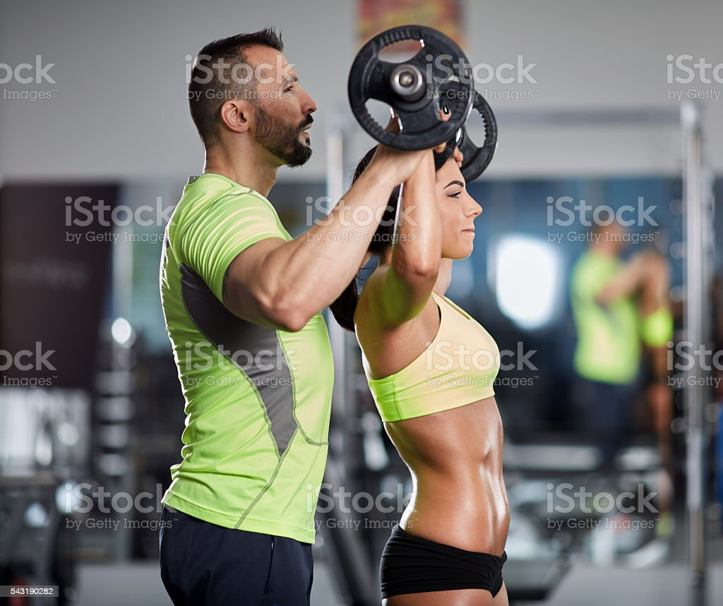Personal trainer at shoulder workout stock photo