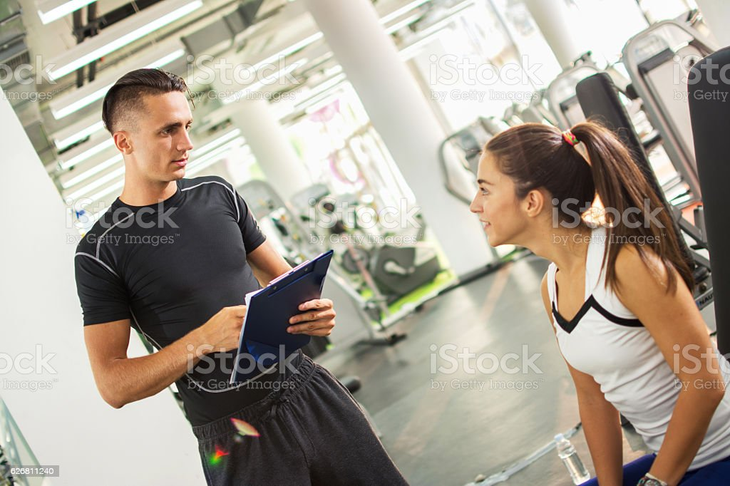 Personal trainer explaining exercise results to his female client. stock photo
