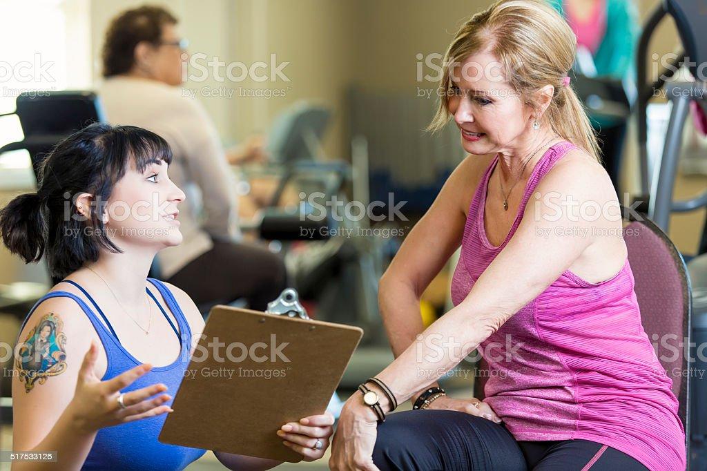 Personal trainer explains exercise plan to senior client stock photo