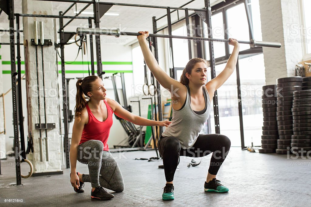 Personal trainer guiding woman doing barbell squats at gym stock photo