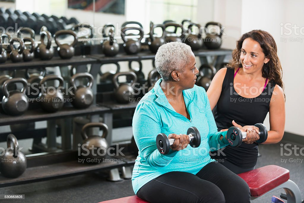 Personal trainer helping African American senior at gym stock photo