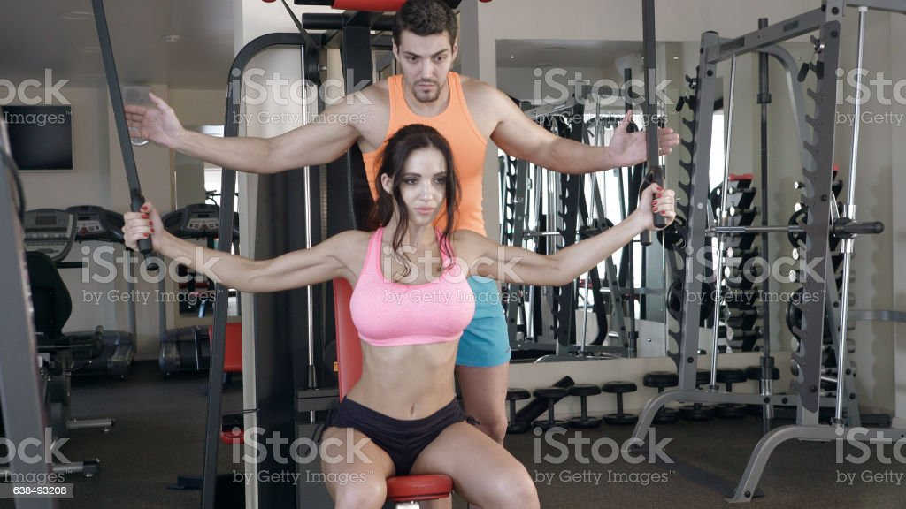 Personal trainer helping girl to train hands in the gym stock photo