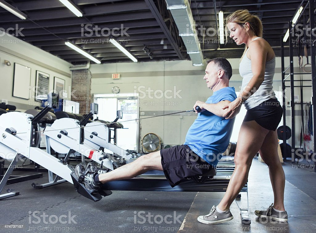 Personal Trainer Helping Man with His Workout royalty-free stock photo