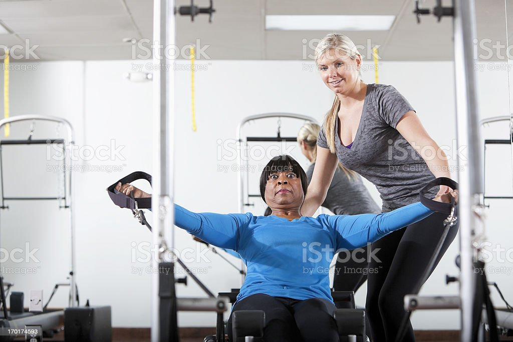 Personal trainer helping woman on pilates reformer stock photo