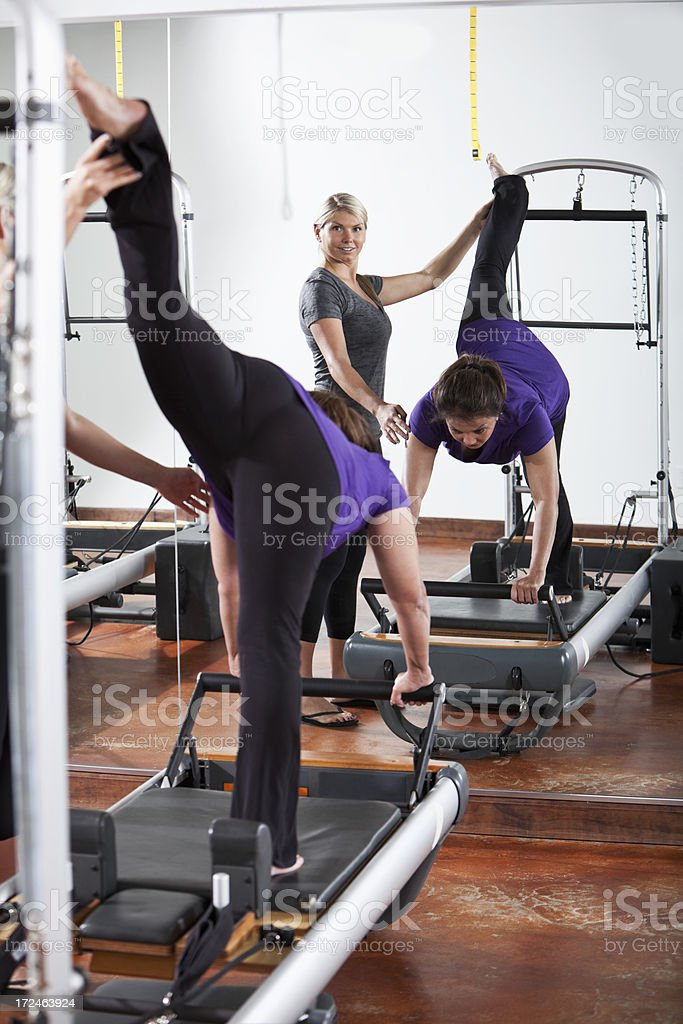 Personal trainer helping woman on pilates reformer royalty-free stock photo