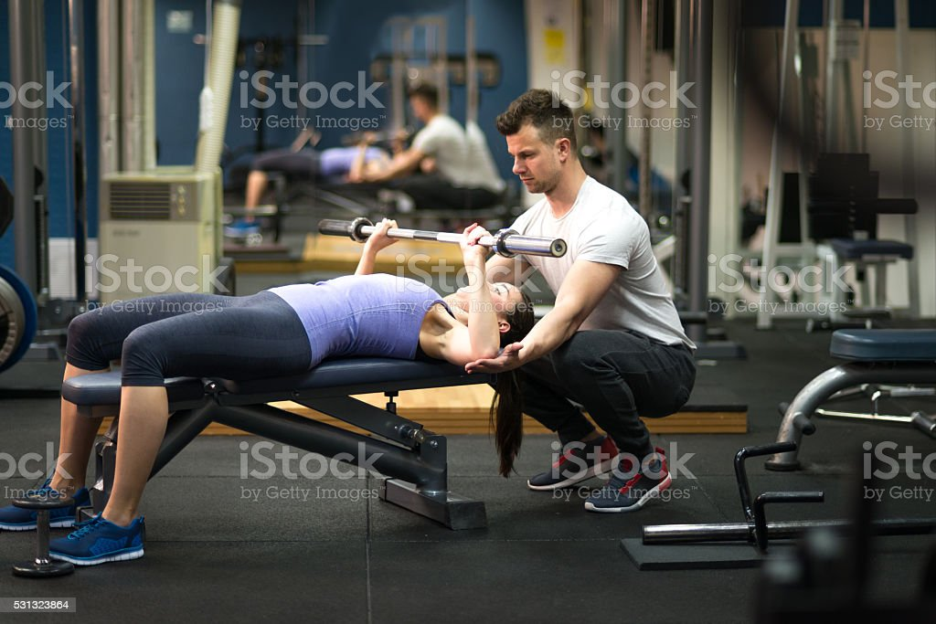 Personal trainer helping woman with her workout stock photo