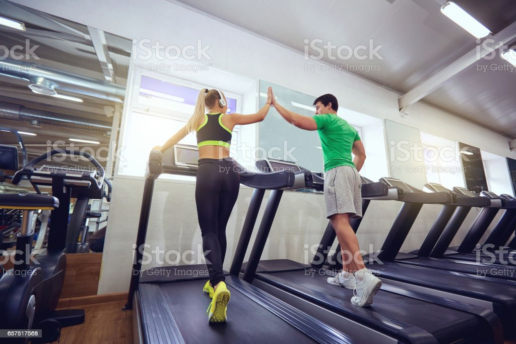 Personal trainer man with athletic girl on a treadmill in the gy stock photo